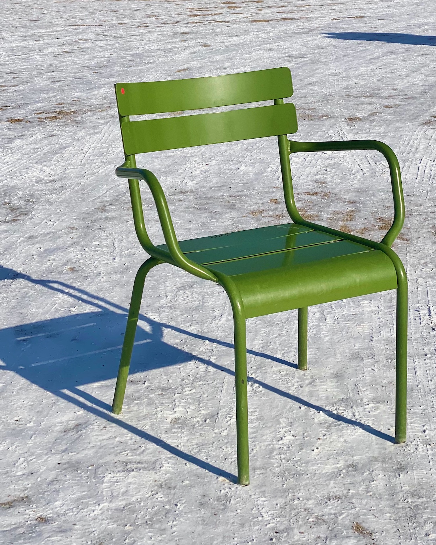 snow in the tuileries garden with a green chair